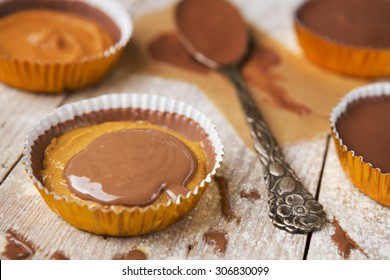 Homemade peanut butter cups on a rustic wooden table.