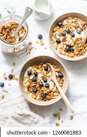 Homemade peanut butter granola with greek yogurt and blueberries on a light background, top view. Healthy energy breakfast or snack. Flat lay