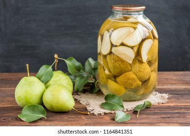 Homemade pear compote and fresh pears with leaves on dark wooden background.