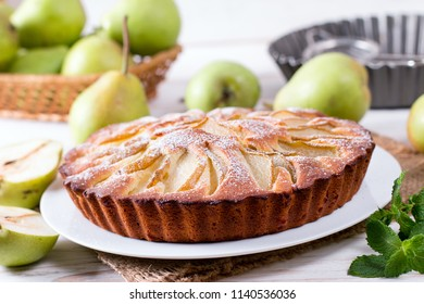 Homemade pear pie on a white table with pears in the background