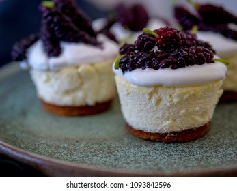 homemade personal cheesecakes with mulberries and cream topping, on top of a ceramic plate