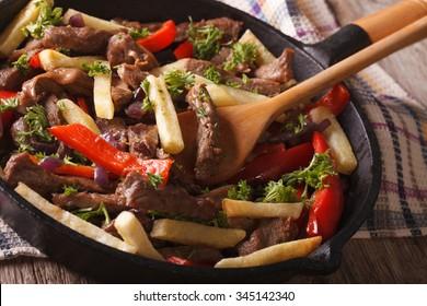 Homemade Peruvian Food: Lomo saltado close-up in a frying pan. Horizontal