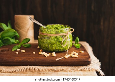 Homemade pesto - organic sauce made of fresh basil, nuts, olive oil, parmesan cheese. Fresh green sauce for pasta in a glass jar on wooden rustic table, sunny light, country style. Copy space.