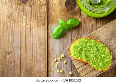 Homemade pesto sauce, bread. Ingredients. Cheese, garlic, basil, pine nuts, olive oil on an old wooden table.