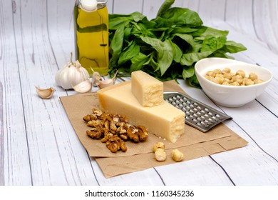 Homemade Pesto Sauce and Ingredients: Cheese, garlic, basil, walnuts and olive oil on white table