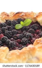 Homemade pie closeup on blackberries.