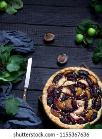 Homemade pie with plums and apples on dark wooden background. Style rustic. Selective focus.