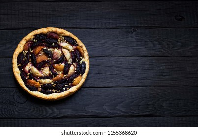 Homemade pie with plums and apples on dark wooden background. Style rustic. Selective focus.  Place for text.