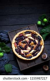 Homemade pie with plums and apples on dark wooden box,fresh apples and plums. Style rustic. Selective focus.