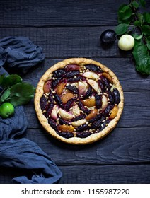 Homemade pie with plums and apples on dark wooden background,fresh apples and plums. Style rustic. Selective focus.