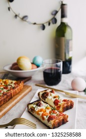 Homemade pie ( quiche) , with ricotta, and fresh colored tomatoes ,cut in slice in a dish with golden fork, glass of wine,rectangular shapes, frontal view ,rustic setup, natural ligt.
