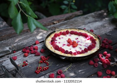 Homemade pie with raspberries sweet baked pastry food on rustic wooden table background in the garden