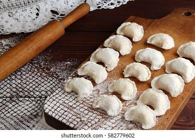 Homemade pierogi vareniki on cutting board - filled dumpling, traditional East European food before boiling. Rustic style