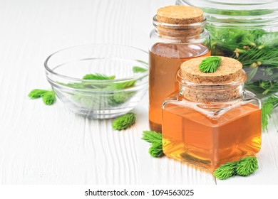 Homemade pine cough syrup for dry irritating throat coughs. Made from green young pine buds and honey.Alternative medicine concept on white wooden table (selective focus).