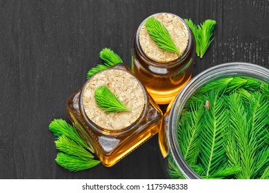 Homemade pine cough syrup for dry irritating throat coughs. Made from green young pine buds and honey.Alternative medicine concept on black wooden table, top view (selective focus).