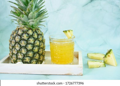Homemade pineapple juice and fresh pineapples as beverages and cooking on the table