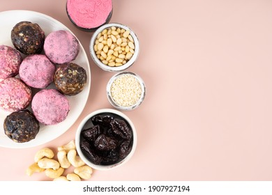 Homemade pink matcha dragon fruit energy balls, top view, healthy sweets made of nuts and date, prunes, sesame, cashew nuts, Pine nuts. Concept vegeterian diet candy brain food. Copy space