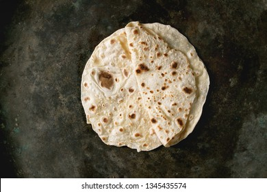 Homemade pita or chapati flatbread flapjack over dark metal background. Flat lay, space