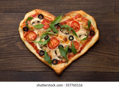 Homemade pizza in heart shape with chicken and mushrooms on rustic wooden table. Italian pizza for Valentines day. Top view.