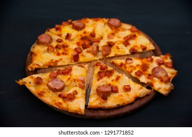Homemade pizza on wooden tray with black background