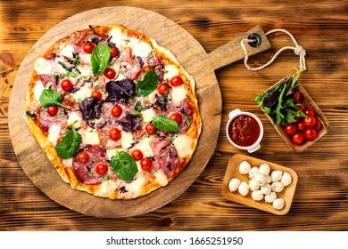 Hausgemachte Pizza mit Salami, Kirschtomate, Mozzarella, Käse, Zwiebeln auf Holzteller, sehr leckere italienische Pizza. Köstliches italienisches Essen. Pizza auf Holzhintergrund.