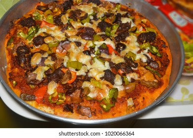 homemade pizza with sausage, cheese, tomato and green pepper