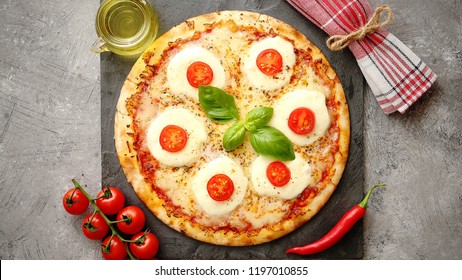 Homemade pizza with tomatoes, mozzarella and basil. Top view with copy space on gray stone table.