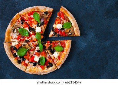 Homemade pizza with tomatoes, mozzarella and basil. Top view with copy space on dark stone table.