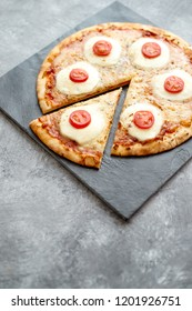 Homemade pizza with tomatoes, mozzarella. Top view with copy space on dark stone table.