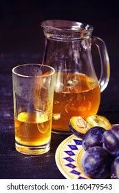 Homemade plum cold drink, plate with plums on rustic wooden background. Close-up vertical photo with selective focus. Side view. Copy place text space for menu design.