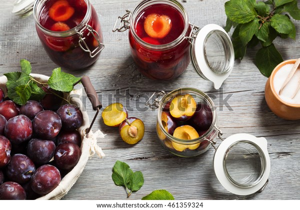 Homemade plum compote on wooden board