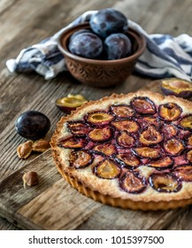 Homemade plum pie on the old wooden background