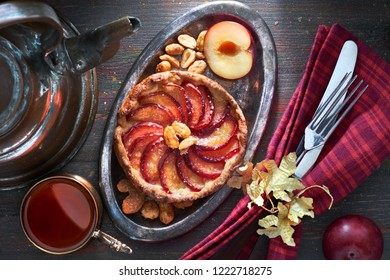 Homemade plum tart served with peanuts on wooden table. Top view with crockery, black tea and copper kettle on dark wood.