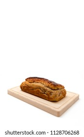 A homemade plumcake standing on a wooden board with a white background