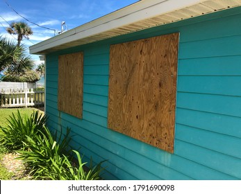 Homemade plywood shutters cover a beach cottage's windows in preparation for an oncoming hurricane in Florida.