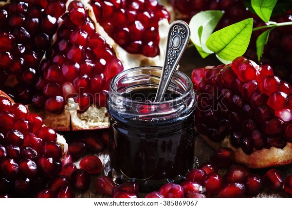 Homemade pomegranate jam in a glass jar with a spoon, fresh open pomegranate on a dark background, selective focus