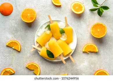 Homemade popsicles with orange juice, ice lollies on sticks, top view flat lay