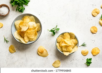 Homemade  potato chips in bowls.  Oven baked crispy potato chips on white background, top view, copy space.