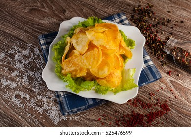 homemade potato chips on a white plate, on a linen towel around preprava is scattered, fast food concept