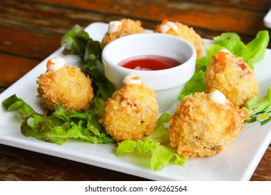 Homemade potato croquettes in plate with dipping sauce on wood background nice and simple, but delicious light food