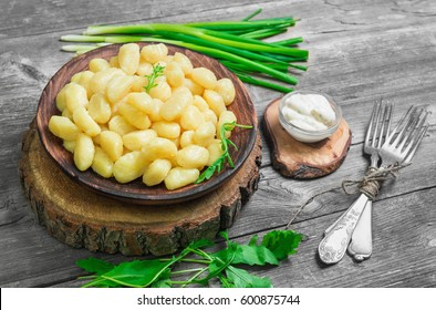 Homemade Potato dumplings Gnocchi in wooden plate. On gray wooden table background ingredients for Potato dumplings Gnocchi Salad of rucola, fresh green onion, sauce, forks.