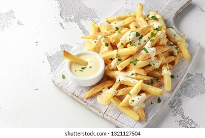 Homemade Potato French Fries with cheese sauce on white wooden board