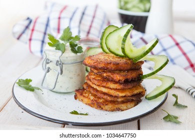 Homemade potato fritters with sour cream and cucumber salad
