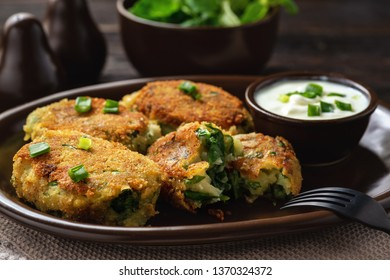 Homemade potato and spinach croquettes with yogurt dip.