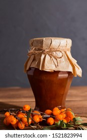 Homemade preservation of fruits and berries, jam, pavidlo from ripe fruits of sea-buckthorn in a glass jar on a wooden background, dark rustic style. Sweet food, dessert, autumn still life