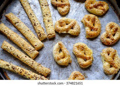Homemade pretzels and sticks with sesame cumin and flax seed in a old pan with patina in landscape top