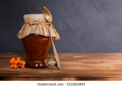 Homemade production preserving fruits and berries, jam, pavidlo from sea buckthorn fruits in a glass jar with a spoon on a wooden background, rustic style. Sweet food, dessert, autumn still life