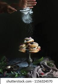 Homemade profiteroles with cream, raspberries and blackberries. Dessert for gourmets. Selective focus. Cooking preparing food dessert women's hands