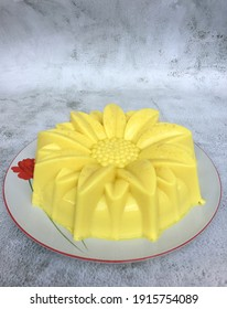 Homemade puding jagung or corn agar-agar pudding on white plate. Made from corn, evaporated milk, coconut milk, jelly powder, sugar and vanilla paste.