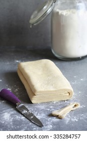 Homemade puff pastry dough on a floured surface
